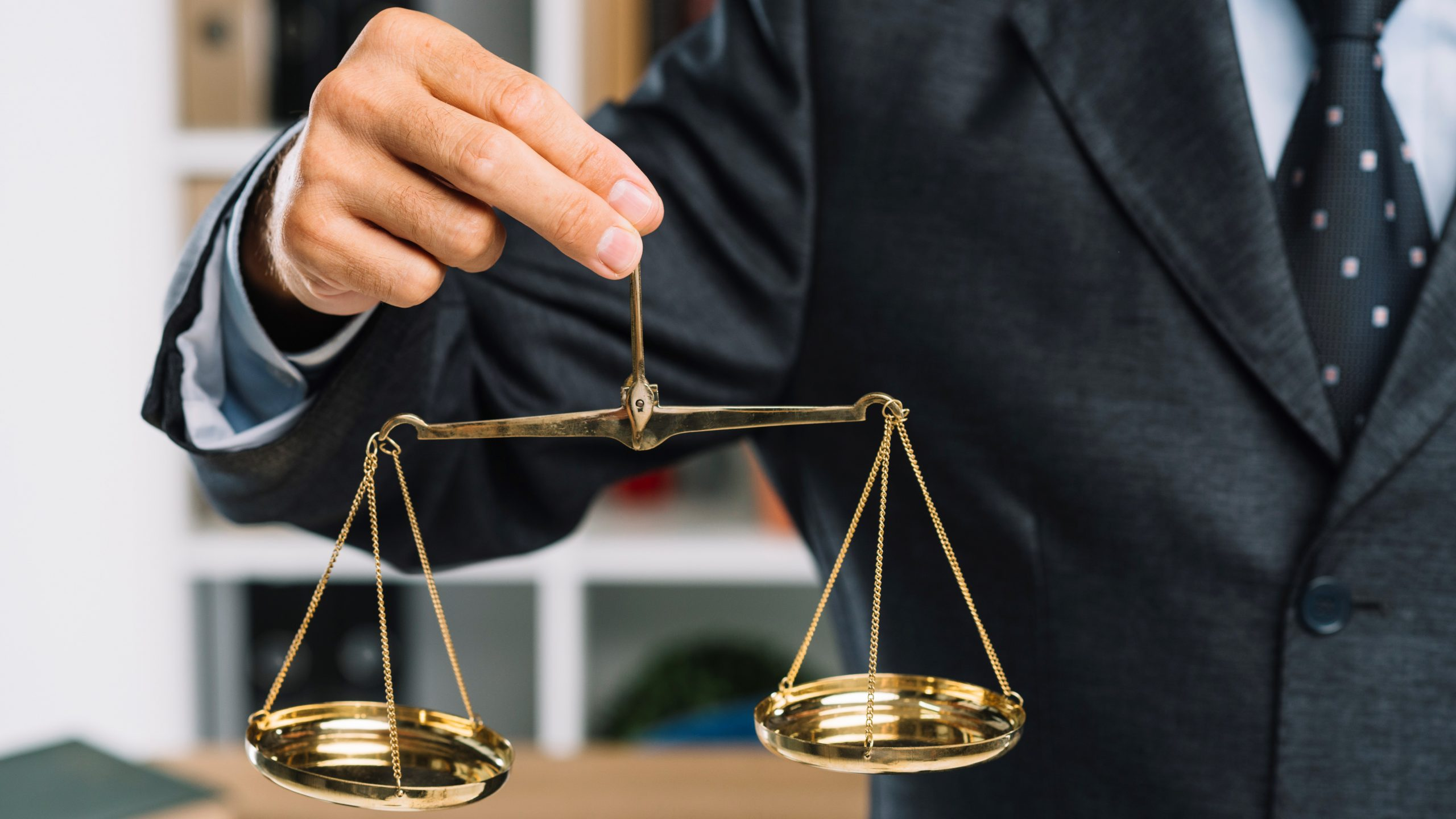 close-up-man-holding-golden-scales-justice-hand